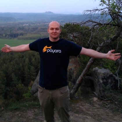 Pavel Pscheidl posing with his arms stretched in front countryside.